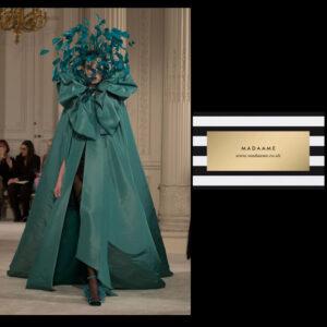 A Haute couture dark green ruffled cloak is fanciful outerwear.