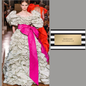 A Haute couture grey silver ruffled gown featuring huge ruffled shoulders and stunning pink sash